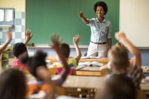 Happy black teacher aiming at school child to answer her question on a class at elementary school.